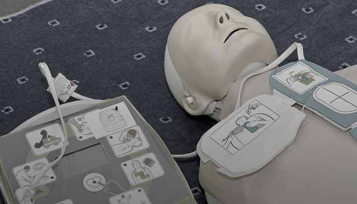 An AED device hooked up to a dummy.