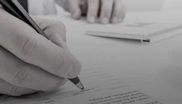 close up of a person signing a paper.