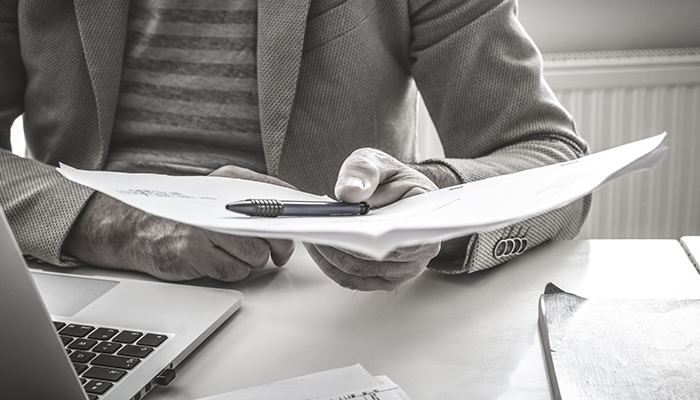 person passing a paper with a pen atop it across the desk.