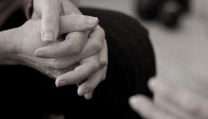 close up of hands clasped, elbows resting on knees.