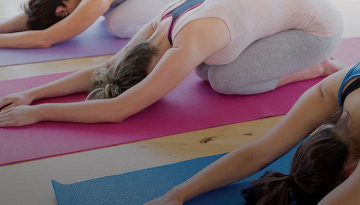 Women on yoga mats in child's pose.