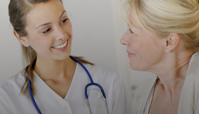 Smiling female nurse talking to a mature woman.