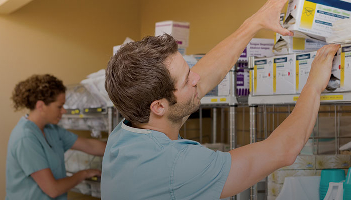 a man in scrubs grabbing supplies off a top shelf.