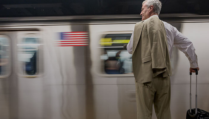 man with a rolling suitcase stands in front of an arriving subway train.