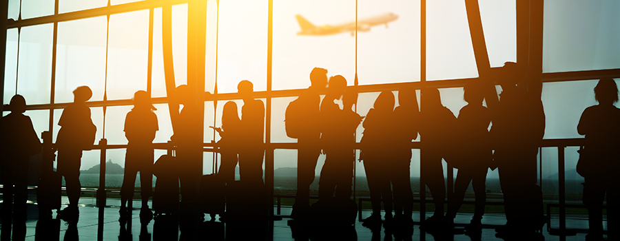 silhouettes of travelers in an airport with an airplane ascending outside.