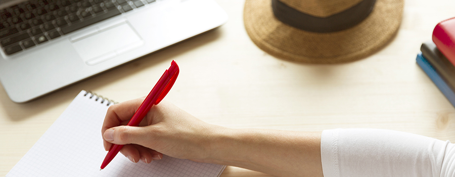 open laptop on a desk with a hat and a woman writing notes on a notepad.